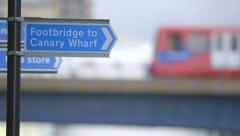 Canary Wharf, London - Footbridge Sign and Train - stock footage