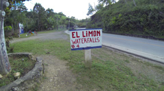 El Limon Falls sign with biker pass by carrying palm leaves Stock Footage