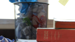 Full Waste Paper Basket With Books Stacked on the Side - stock footage