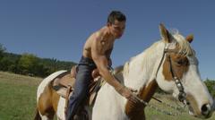 Shirtless Man Petting Horse Stock Footage