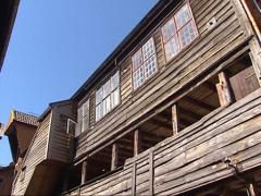 Low angle view + pan Old-style wooden houses in a narrow street in Bryggen Stock Footage