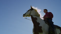 Man Riding White & Brown Horse, Shot From Below Stock Footage