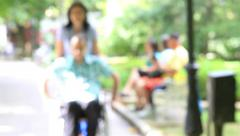 Young man in wheelchair in the city park Stock Footage