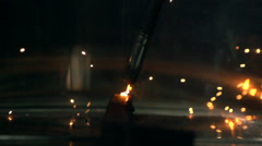 Stock Video Footage of welded iron in slow motion, light particles become airborne, reflection of th