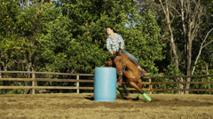 Woman Rides Brown Horse Around Blue Barrel, Shot from Below Stock Footage