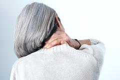 cervicalgia in an elderly person - stock photo
