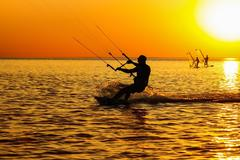 silhouettes of a windsurfers - stock photo