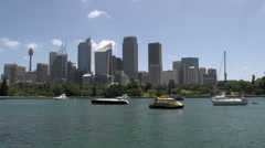 Sail boats and small water taxi in front of Sydney skyline Stock Footage