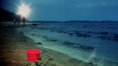 People on the beach walking and red toy bucket at sunset Stock Footage