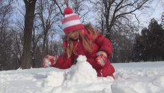 Little Girl Playing in Snow in Winter, Child Making Snowball for Snowman in Park Stock Footage