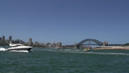 Stock Video Footage of Speedboat and small water taxi passing by in front of the harbour bridge