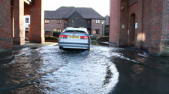 The English floods 2014 (car drives into flooded court yard) Stock Footage