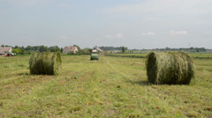 Straw bales agricultural machine gather hay near village houses Stock Footage