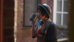Inside Looking Outdoors Into A Courtyard At A Young Woman Drinking Coffee - stock footage