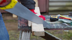 Carpenter sawing plank Stock Footage