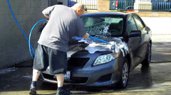 Man Washing Soaping Down Hood Of Car At Car Wash Stock Footage