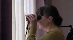 Curious woman spying on neighbors with binoculars, looking through the window Stock Footage