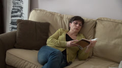Woman reading a book on a couch at home, novel, relaxing Stock Footage