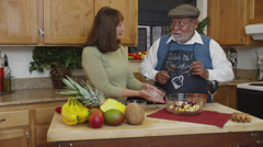 Retired Couple Tossing Fruit Salad in Kitchen Stock Footage