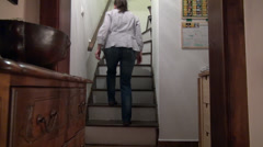 Woman having low back pain while walking up the stairs Stock Footage