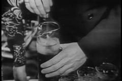 Medium shot of man mixing beverage in pitcher, 1950s Stock Footage
