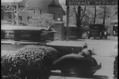 Taxi driver pulling up in front of house and removing hat box from car, 1930s Stock Footage