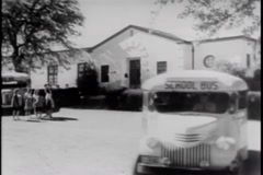 Bus driver leaving school with bus load of students, 1940s Stock Footage