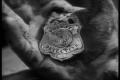 Close-up of bloody hand clutching private detective badge - stock footage