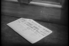 Newspaper sliding under door, 1940s Stock Footage