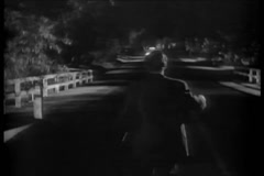 Rear view of man waving hands to stop bus at night, 1940s Stock Footage