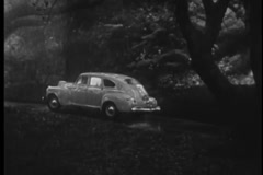 Car driving up road to house in the rain, 1940s - stock footage