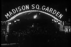 Crowd milling beneath neon Madison Square Garden marquee, 1930s - stock footage