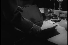 Man looking through documents on desk, 1940s Stock Footage