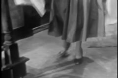 Low angle shot of woman picking up clothing from floor, 1950s Stock Footage
