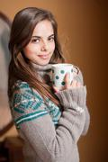 portrait of a beautiful young brunette woman holding a cup of hot beverage. - stock photo