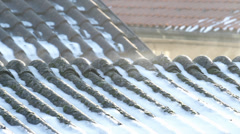 Evaporation on asbestos roof covering in the morning on a cold winter day Stock Footage
