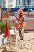 Worker on road repair in dubai marina Stock Photos