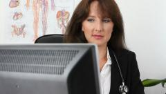Female doctor at her desk Stock Footage
