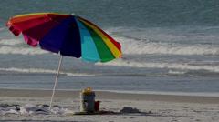 Rainbow Colored Umbrella on the Beach Stock Footage