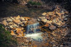 Waterfall created to artificially with herbs near the Carpathians Stock Photos