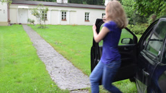 Hasten blond lady get out from car and run toward house Stock Footage
