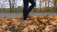People step through autumnal dried leaves coated path Stock Footage