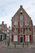 traditional ducht house with red window shutters - stock photo