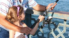 Male hands help little girl to keep fishing rod at sunny day Stock Footage