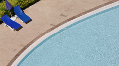 Top view to blue pool and two loungers at sunny summer day Stock Footage