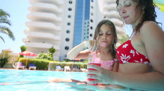 Mother and her daughter drinking cocktail from glass in pool Stock Footage
