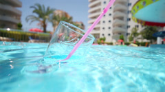Glass with pink soda straw floats in blue water of pool Stock Footage