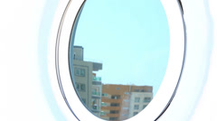Mother and her little daughter look out from round window Stock Footage