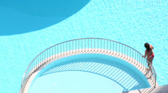 Young woman in swimsuit goes near railing of pure outdoor pool Stock Footage