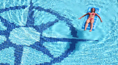 Beautiful girl in swimsuit floats on air mattress in pool Stock Footage